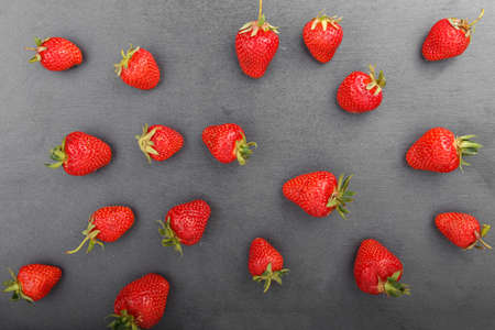 A ripe strawberry is scattered on the black background of a slate board. view from above. Space for text
