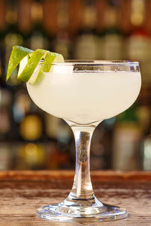 Daiquiri cocktail with rum and lime juice. Traditional taste. The cocktail is on the bar in a pub or restaurant. Space for text. Stock Photo