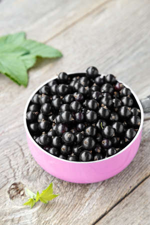 crop currant. currants in a pink pot on a wooden background. in the background is a currant and leaves. 版權商用圖片