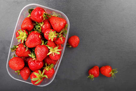 Strawberries in plastic box on a slate board, top view