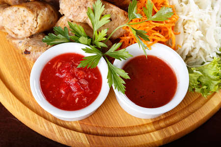 meaty: Fried sausage with sauces on a plate with vegetables, close-up. Background for menu or advertising