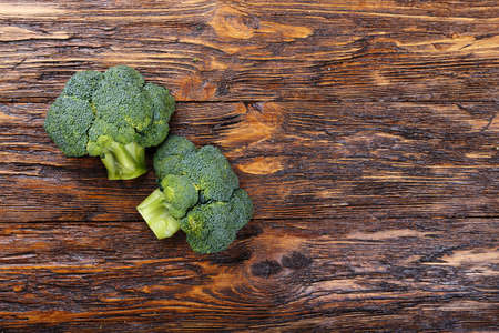 Inflorescence of raw broccoli on a wooden table, With space for text, horizontal shot Stock Photo