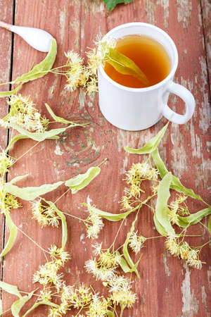 tea with a linden on a wooden table, around the cups scattered linden blossoms