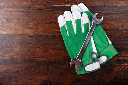 Working gloves and a screwdriver on a wooden dark brown background, space for text Stock Photo