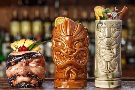 Set of three tropical cocktails - pina colada, rum runner and rio punch. Cocktails stand in a bar on a blurry background of alcohol. Menu image