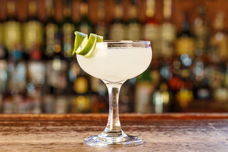 Traditional cocktail daiquiri, image for the menu. The cocktail stands on the background of the bar counter. Space for text Stock Photo