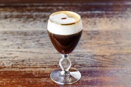 """""""아이리쉬 커피""""는 아이리시 위스키, 블랙 커피, 휘핑 크림 및 갈색 설탕을 기본으로 한 크림과 함께 칵테일로 분류되는 커피 음료입니다."""