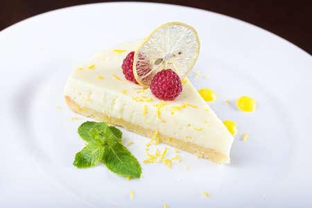 custard slice: piece French lemon tart, garnished with fresh raspberries, mint and slice of lemon
