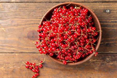 Red currant in a clay plate on a brown wooden kitchen table. top view