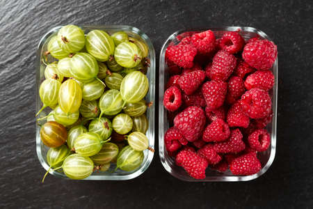 vitamin rich: Raspberries and gooseberries, mix of summer berries in glass plates on a black slate background Stock Photo