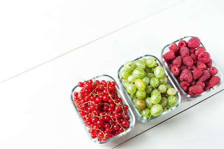 Mix of berries on a white background, summer harvest of raspberry, red currant and gooseberries, prepare berry dessert