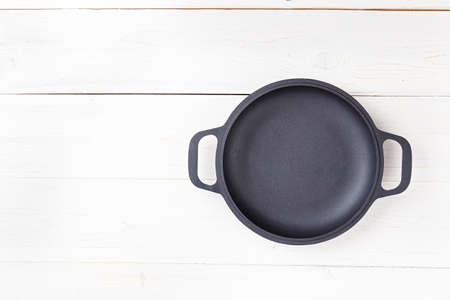 Empty frying pan place for text, on a white wooden background Stock Photo