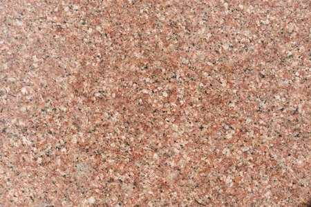 Red granite slab with black patches, background. Kitchen wall or bathroom