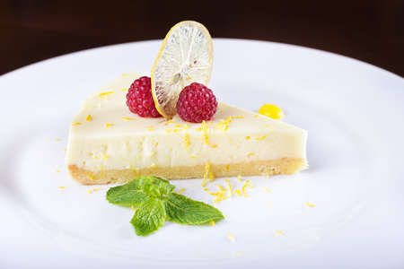 bakery products: piece French lemon tart, garnished with fresh raspberries, mint and slice of lemon