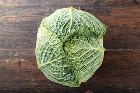 savoy cabbage: head of fresh Savoy cabbage on a brown wooden background, top view