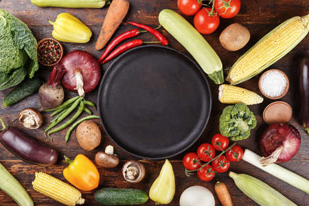Summer vegetables on a brown wooden background. carrots, tomatoes, onions, corn, peppers. place for text on a empty frying pan in the center