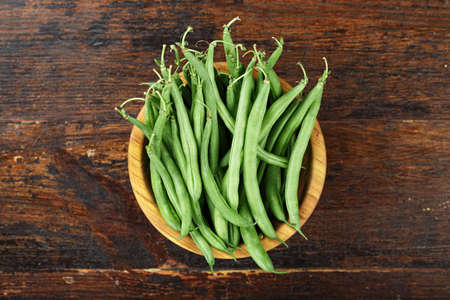 Fresh green beans n wooden bowl on dark wooden rustic background, top view