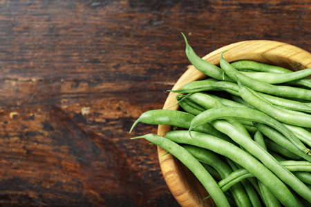 Fresh green beans n wooden bowl on dark wooden rustic background, top view, space for text Reklamní fotografie