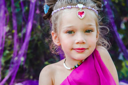 small European girl in oriental dress, crimson color, in a tent outdoors, harmony, staged shooting Stock Photo