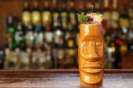 Mai Tai is a refreshing cocktail based on rum, orange liqueur, almond syrup and lime juice. Cocktail on the shabby wooden background of the bar counter. Cocktail in a glass in the form of a Moai statue