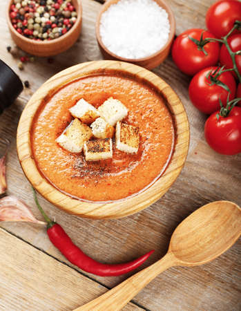 gazpacho: Spanish tomato soup gazpacho in a plate on a wooden background. next to it are tomatoes, peppers, spices and wooden spoon
