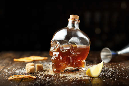 Glass or bottle in the form of a skull with a cocktail for Halloween, on the bar