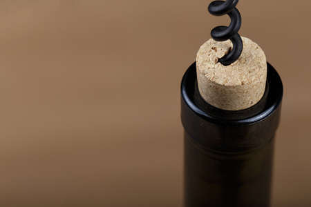 a bottle of wine is opened with a corkscrew, a corkscrew is screwed into a bottle Stock Photo