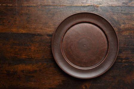 empty flat clay plate on a brown wooden background, top view, space for text  Stock Photo