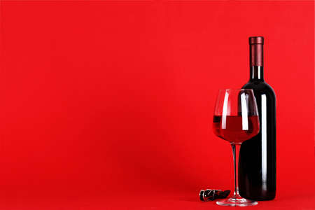 a bottle of wine and a glass on a red background with space for text