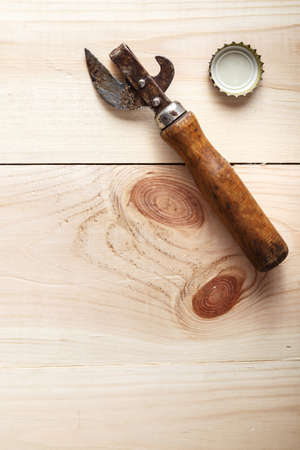 Vintage Opener near the lid of beer, on a wooden background, space for text