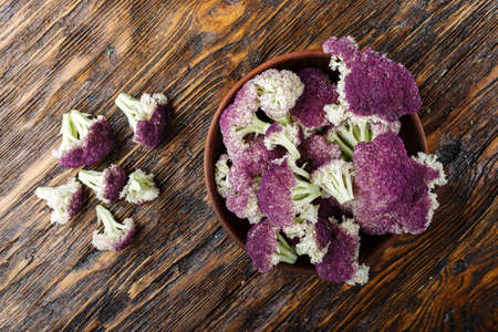 purple cauliflower in a clay plate, on a wooden table Stock Photo