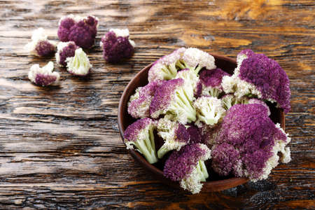 Purple cauliflower in a clay plate, on a wooden table
