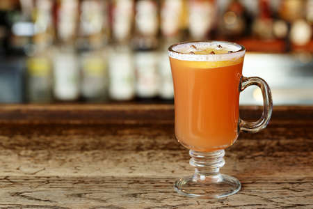 Hot alcoholic grog with orange and seasoning cloves on a wooden bar counter