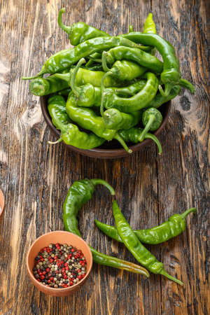 green chili peppers placed in a clay plate on a brown wooden table. with space for text
