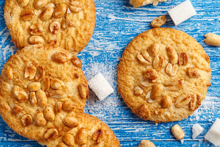 appetizing homemade cookies with peanuts on a blue shabby wooden background, biscuits broken. top view, space for text
