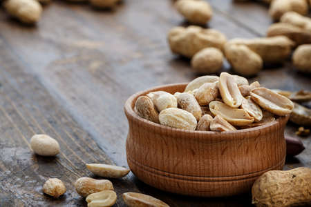 peanuts in a wooden plate on the table, a snack for beer