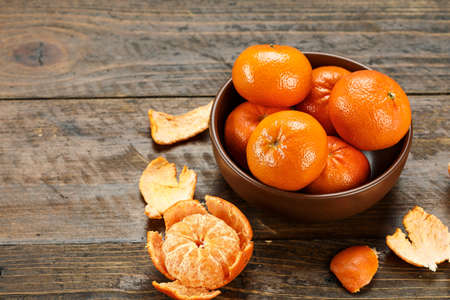ripe whole and peeled tangerines in a plate on a wooden table