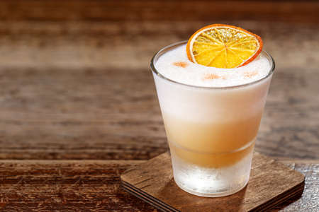 A classic recipe for whiskey  sour - with bourbon, cane syrup and lemon juice, garnished with orange. Traditional aperitif. Space for text Foto de archivo