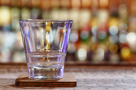 Empty glass on a wooden worn background of a bar, on a blurry background of bottles with alcohol Stock Photo