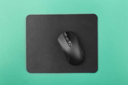 black computer mouse on a green background, top view