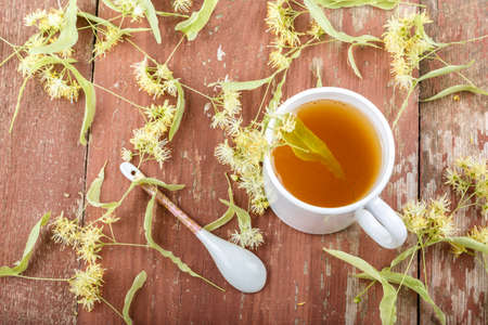 Lime tea in a white cup and flowers with linden leaves scattered on a wooden background