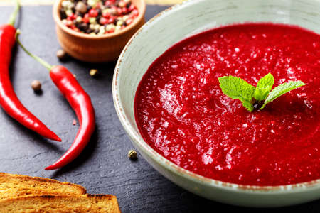 Italian tomato soup gazpacho on a black background, next to lie, tomatoes and spices, view over