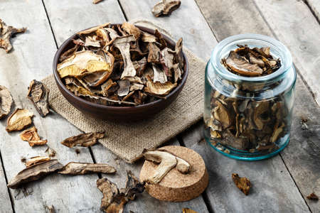 dried mushrooms boletus sliced, on a plate, on an old wooden background