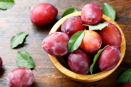 ripe plums in a wooden plate, with leaves, on a wooden background