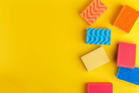 Set multi-colored sponges on a yellow background, space for text