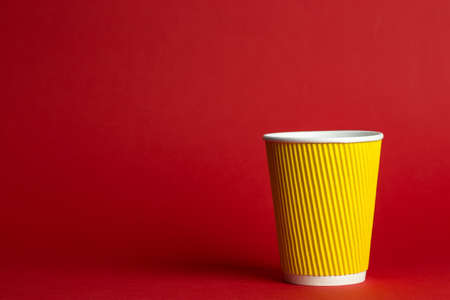 coffee to go in a disposable cup on a red background, place for text  Stock Photo