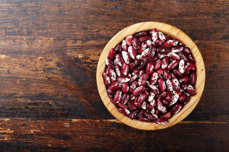 raw violet beans in a plate on a wooden background, top view Stock Photo