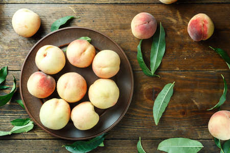 harvest of ripe peaches on a table in a clay plate, space for text