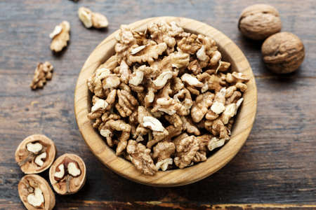 walnuts on a wooden background, in a plate. a useful nutritious protein product. place for text