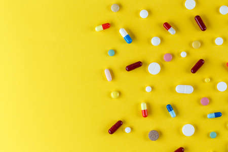different pills and capsules scattered on a yellow background, space for text Foto de archivo - 102819486